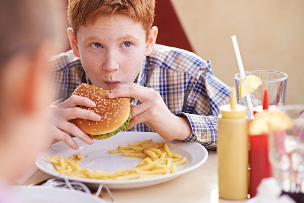 Teenage-boy-eatng-hamburger-iStock_35442532_XXLARGE