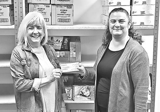 Teri Mason, left, of FORK presents a $1,000 donation to Pastor Andrea Fluegel of Prince of Peace Lutheran Church in support of the Weekend Backpack Program in Eagle River, Land O' Lakes and Phelps elementary schools